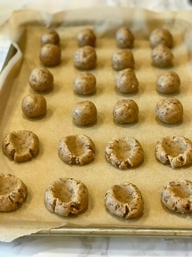 Cookie dough portioned out on baking tray with thumbprints indented.