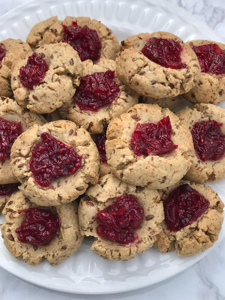 A plate of cookies with cranberry jam in the center.