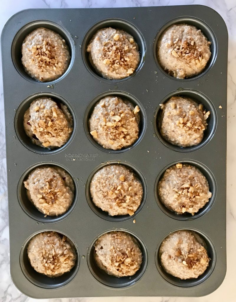 Oatmeal muffins in tins with streusel topping, ready to bake.