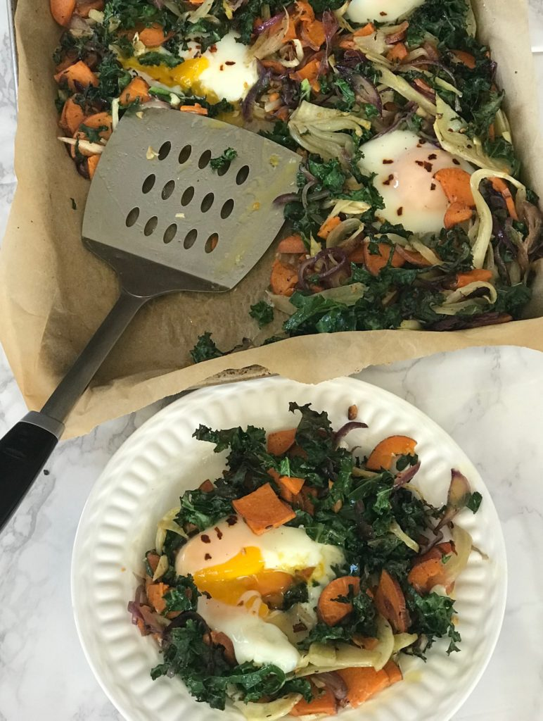 Eggs and veggies cooked on a sheet pan lined with parchment paper.