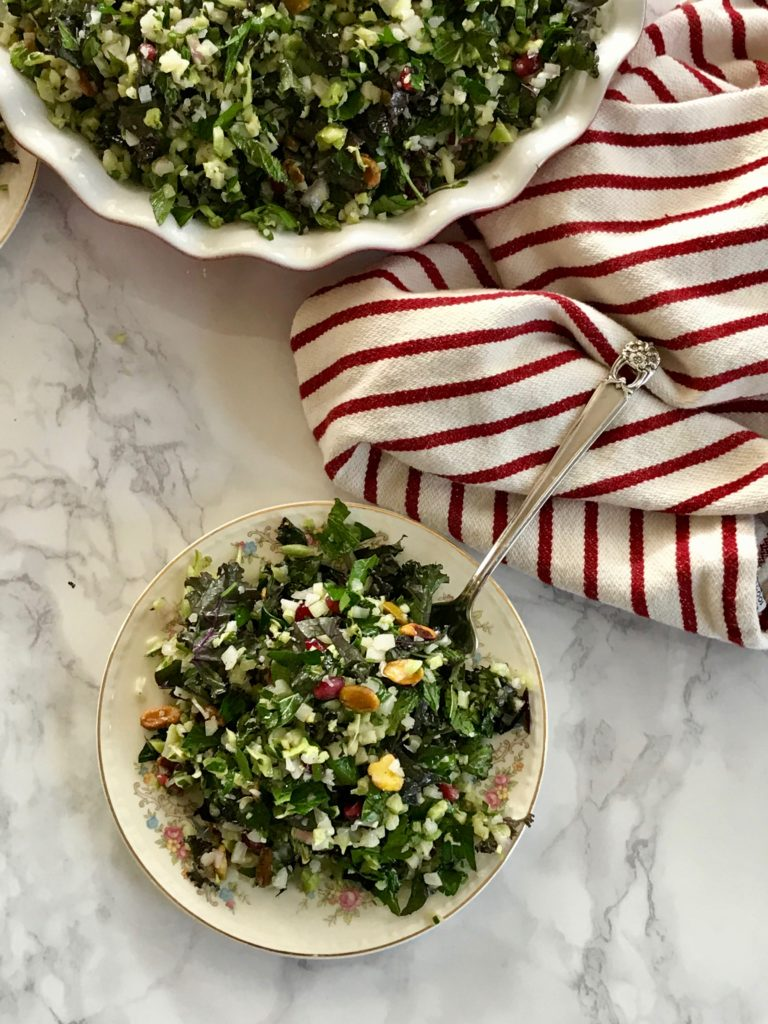 Bowl of greens with pomegranate seeds and nuts.
