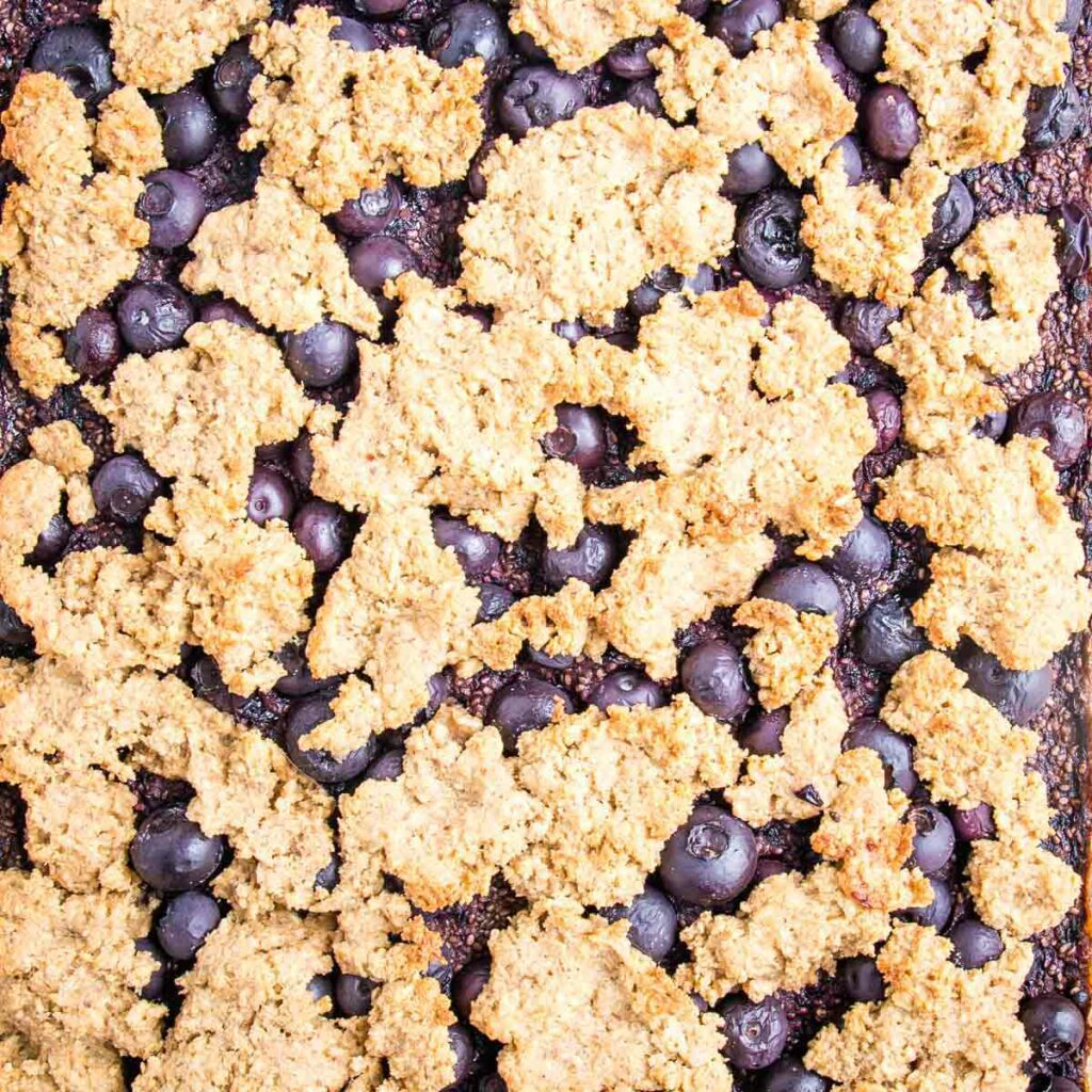 Up close shot of blueberry crumble right out of the oven.  You can see some of the cooked blueberries and the jammy inside through the cracks in the crispy topping.