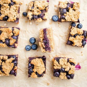 Blueberry Bars, cut into squares on a piece of parchment paper. One is turned on its side so you can see the jammy center.
