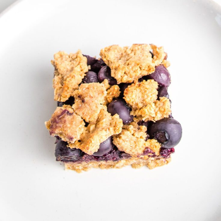 Close up of one blueberry crumble bar. You can see the jam and the fresh blueberries through the crispy top.