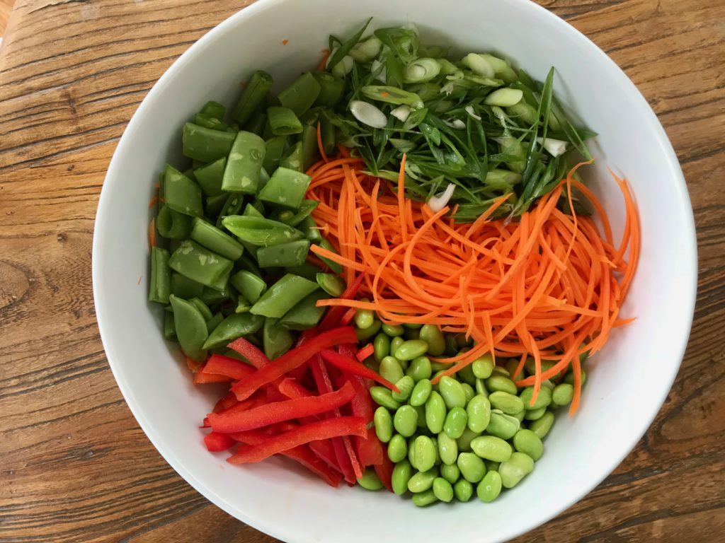 bowl full of prepped veggies:  edamame, carrots, red peppers, scallions, snap peas