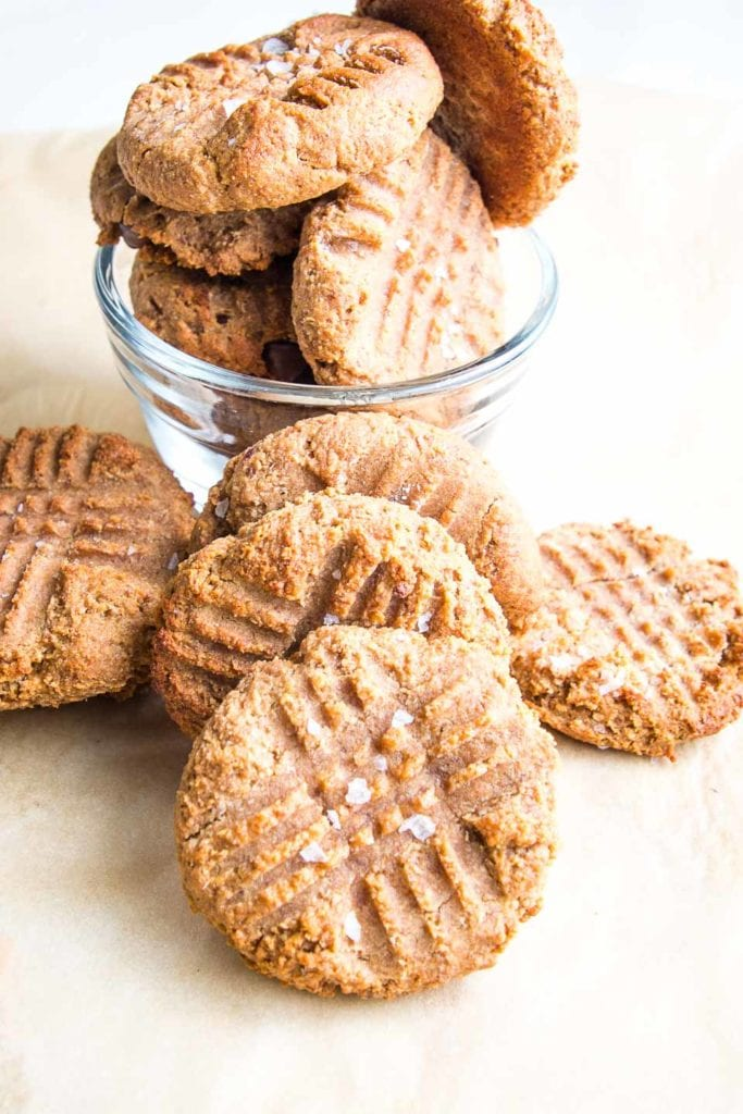 Peanut butter cookies with fork indentation making cross-hatch pattern. A few cookies in a small glass dish and several more leaning up against the bowl.