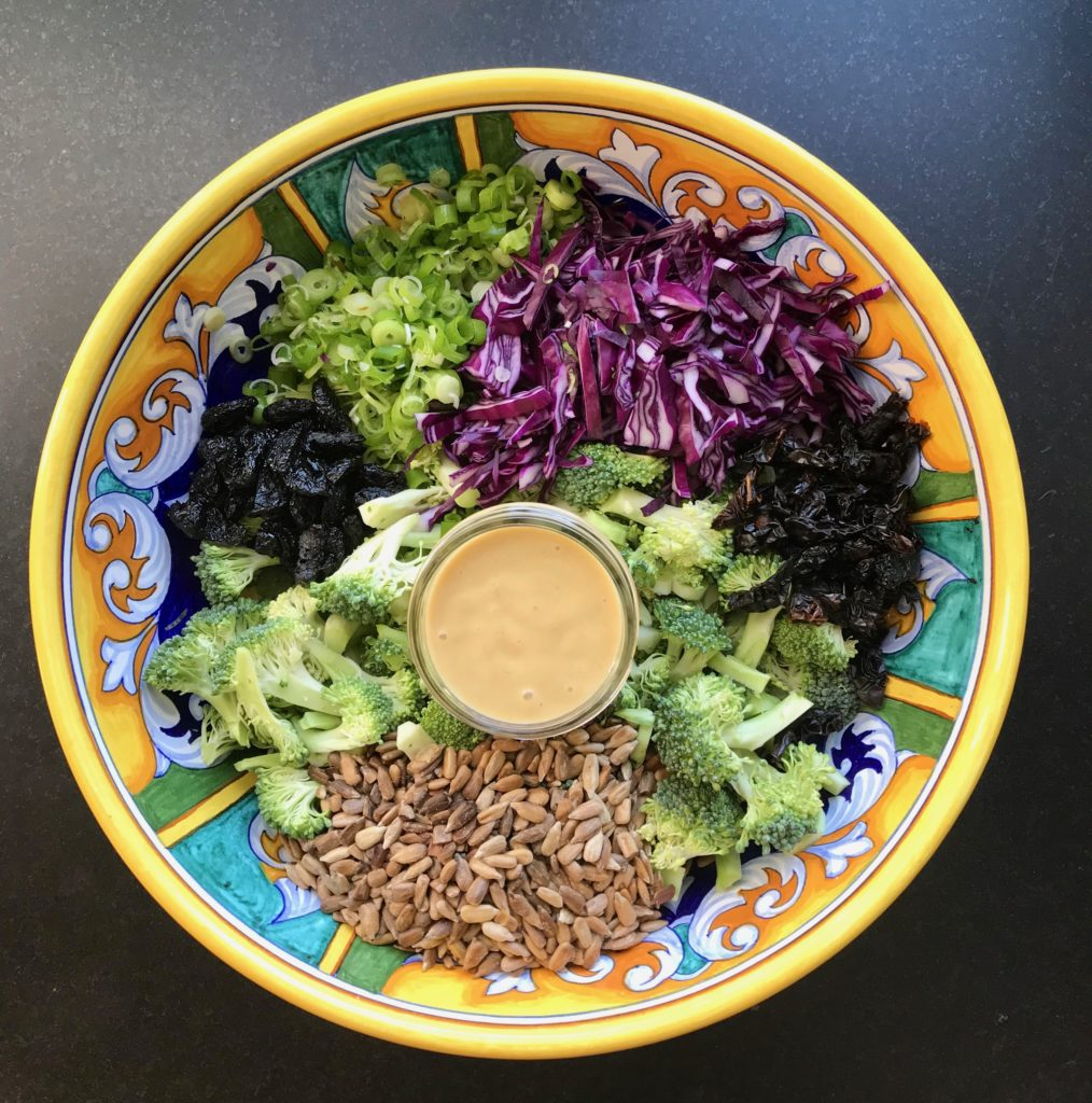 Large brightly colored bowl with chopped scallions, purple cabbage, sunflower seeds, broccoli florets, sun dried tomatoes and dried cranberries iwth a glass jar of dressing in the center.