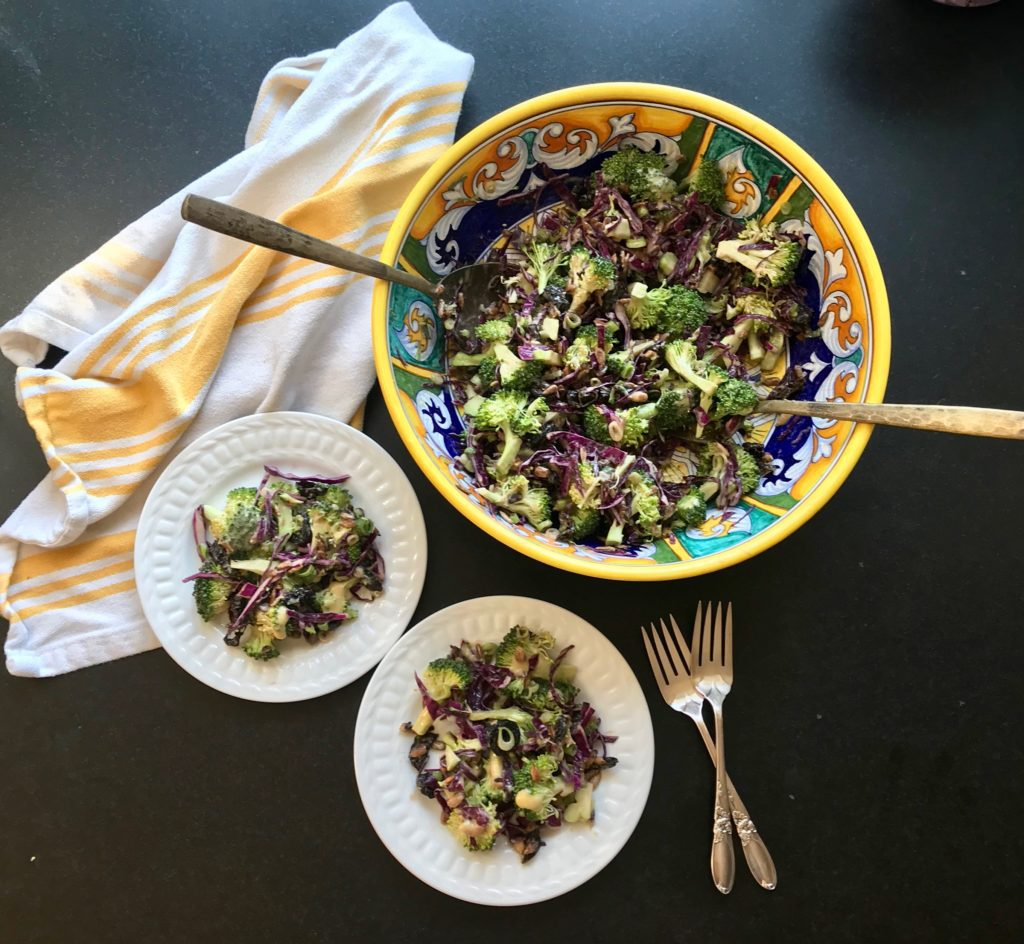 Chopped salad in a brightly colored serving bowl, a tea towel with yello stripes and two small white plates filled with same salad.