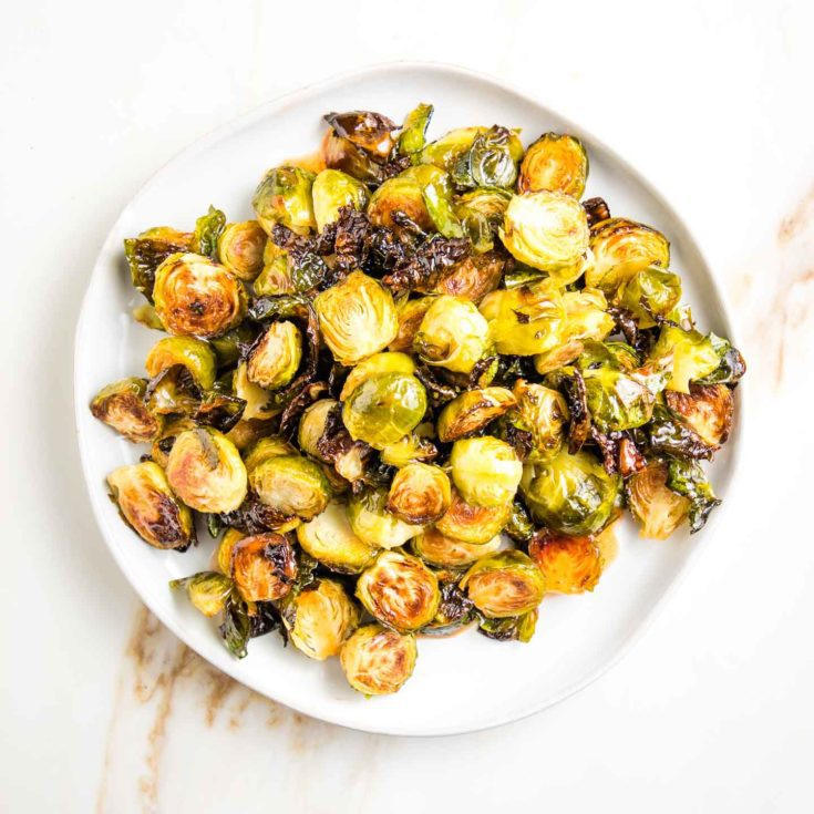 Round plate filled with roasted brussels sprouts with sweet and spicy drizzle