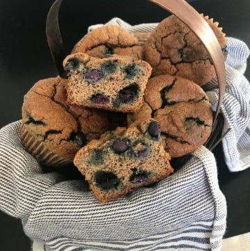 Tea towel lined basket filled with blueberry muffins.