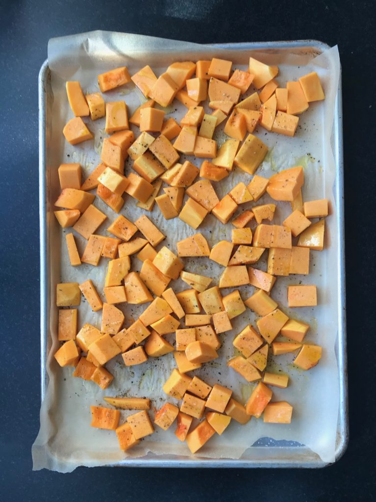 A sheet pan lined with unbleached parchment paper and filled with cubes of butternut squash