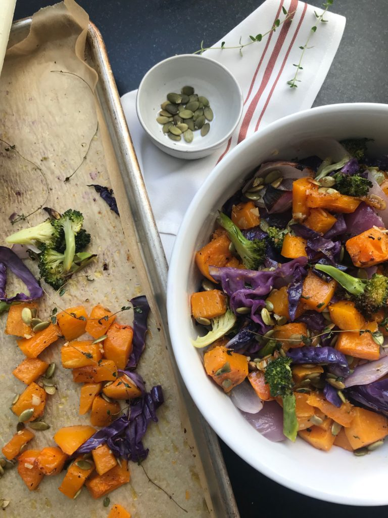 A sheet pan lined with parchment paper almost empty with a large white bowl of roasted veggies and a small bowl of pepitas.