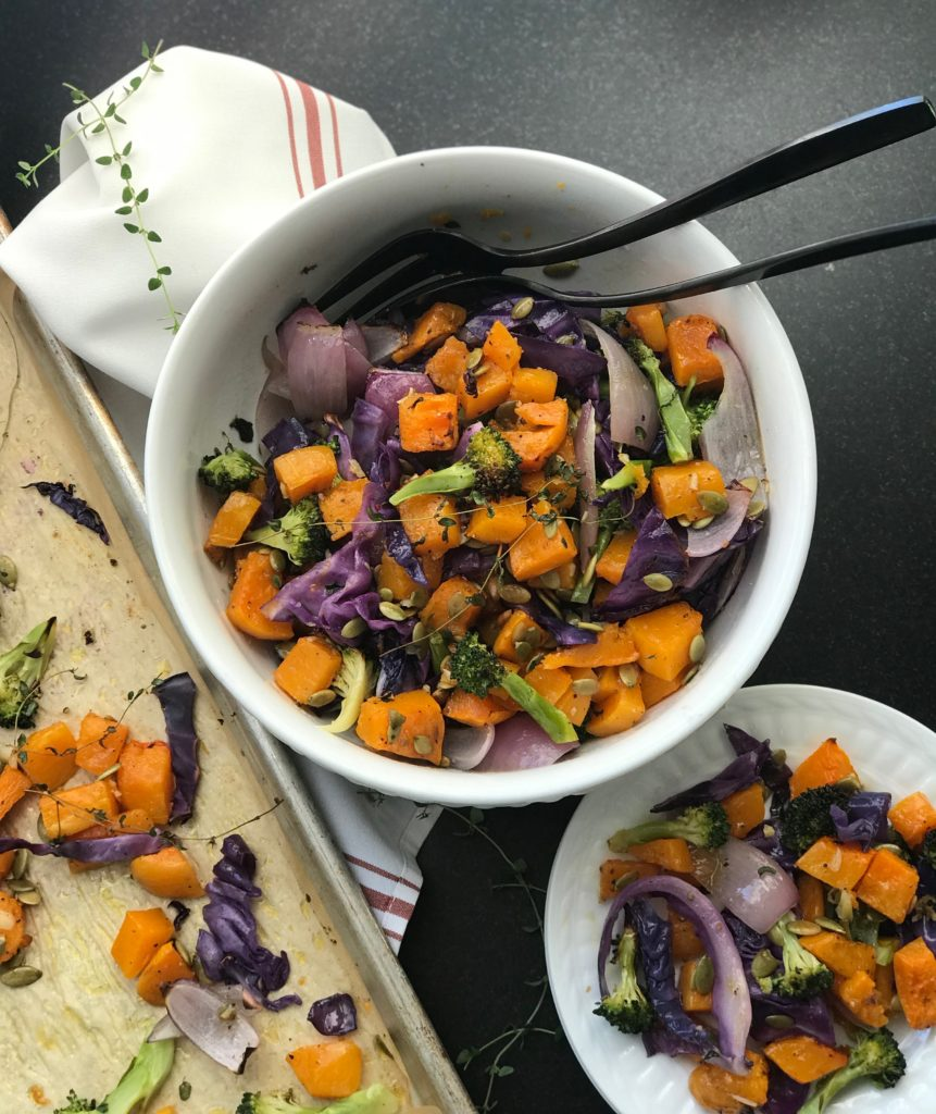 Sheet pan of roasted veggies alongside a bowl of squash, broccoli, onions and cabbage plus a small bowl of the same.