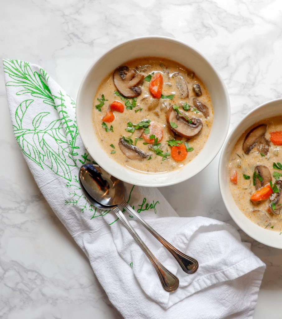 Spoons, napkin and two bowls of creamy mushroom soup