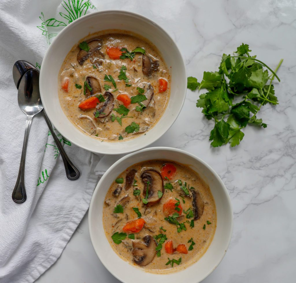 Two bowls creamy soup with mushroom, carrots and chopped greens.