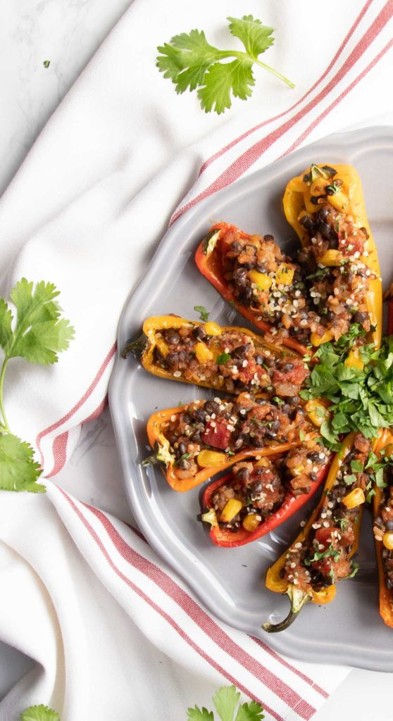 A plate of lentil stuffed mini peppers garnished with cilantro.