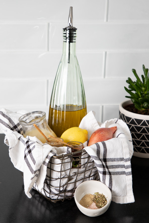Ingredients for everyday salad dressing in a basket: olive oil, lemon, shallot, spices, lemon juice.