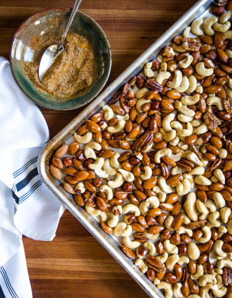 Spice mixture sprinkled onto a tray of assorted nuts