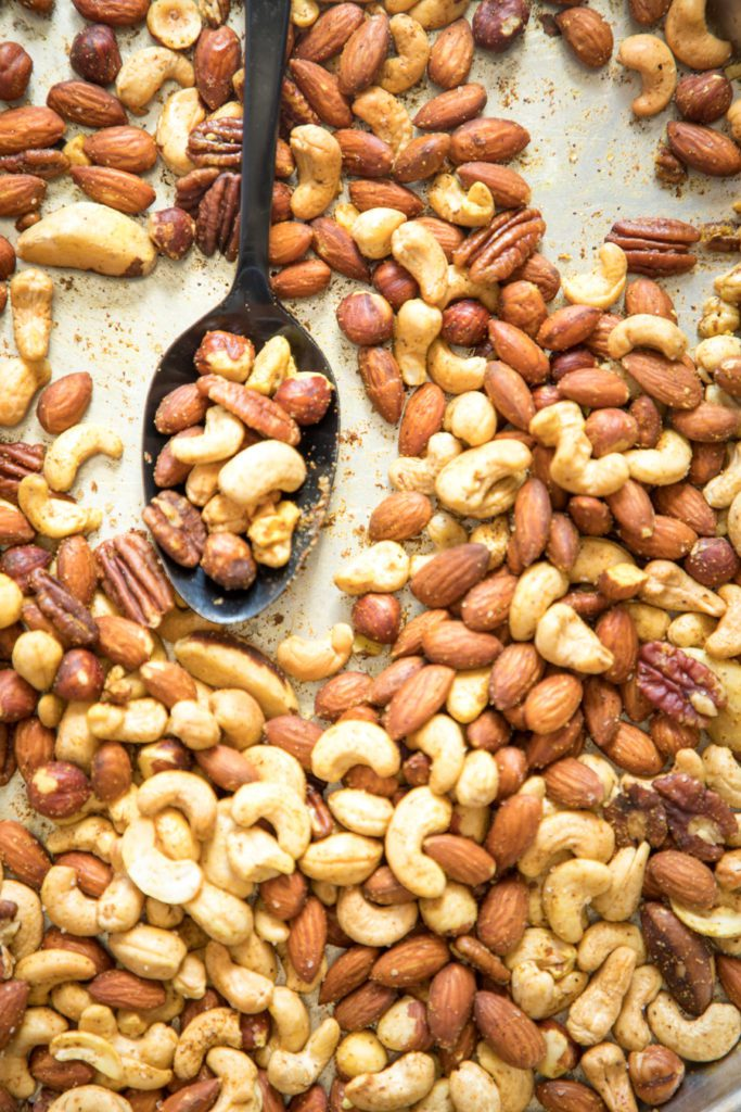 A spoonful of roasted spiced nuts on a baking tray.