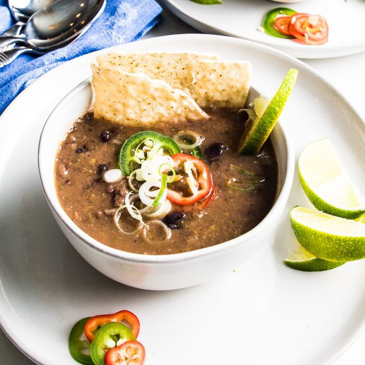 Bowl of black bean soup with toppings