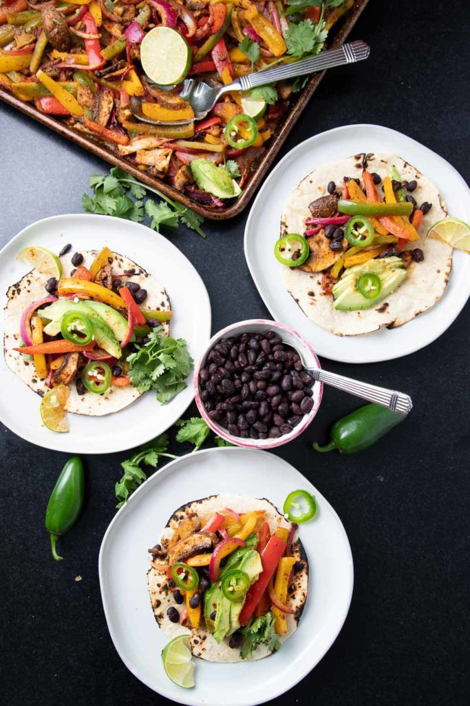 Roasted veggies on top of tortillas with bean and avocado