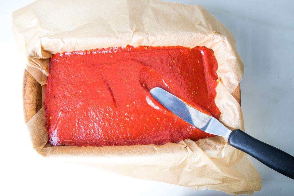 Spreading a ketchup like glaze on top of meatloaf