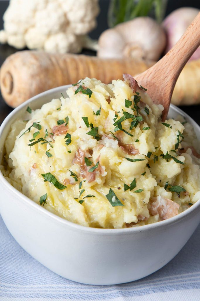 Bowl of chunky potatoes with skins on sprinkled with chopped parsley
