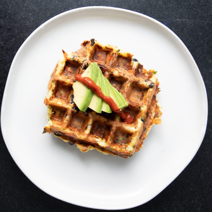 Square waffle with avocado and a drizzle of sriracha
