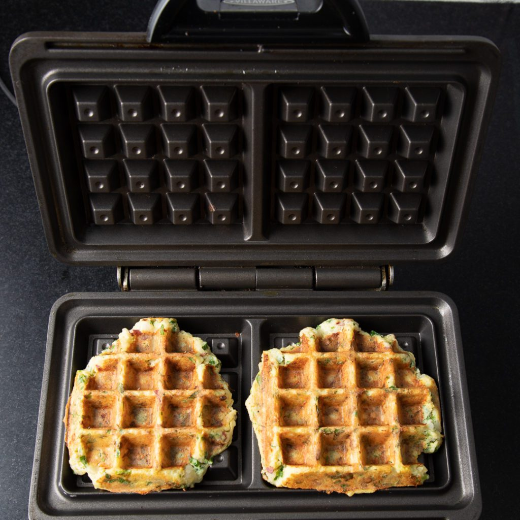 Finished waffles in iron with large specks of green herbs.