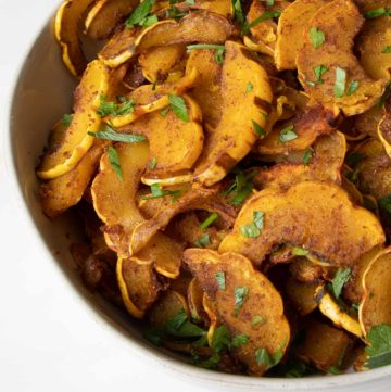 Bowl full of half moon shaped orange delicata squash with fresh green parsley sprinkled on top