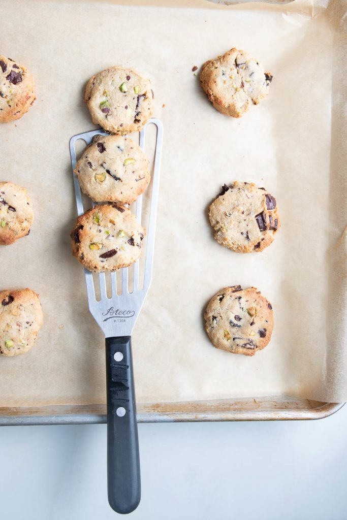 Parchment lined baking tray with chocolate chip cookies straight from the oven.
