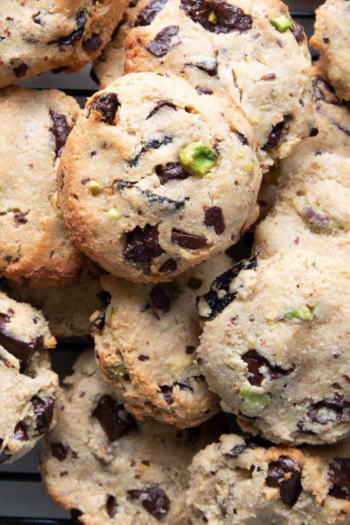 A pile of gluten-free vegan cookies with pistachios and chocolate chunks.