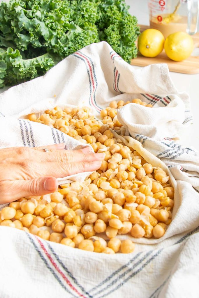 A kitchen towel is used to rub the skins off the chick peas