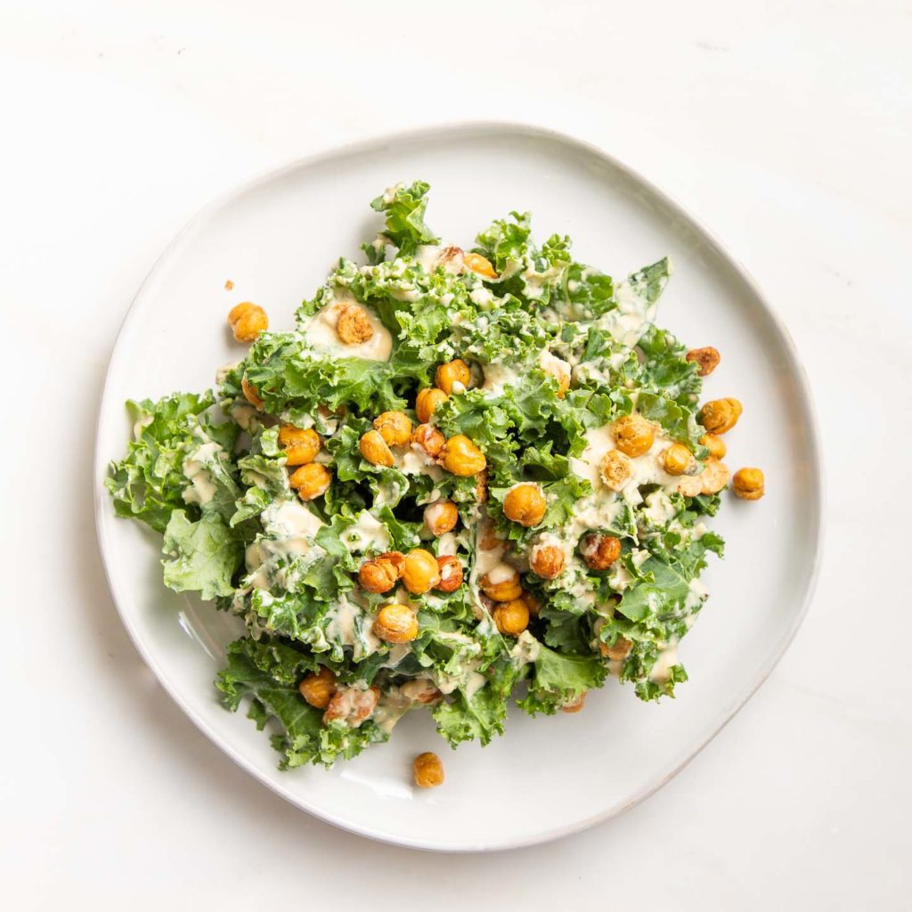 A plate with kale, creamy dressing and roasted chick peas.