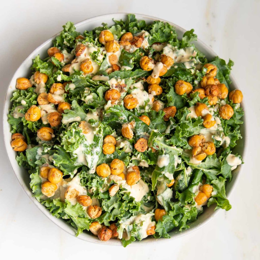 Big bowl full of bring greens, creamy dressing and roasted chick peas