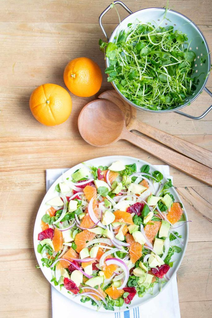 Plate of orange and fennel salad with a colander of watercress