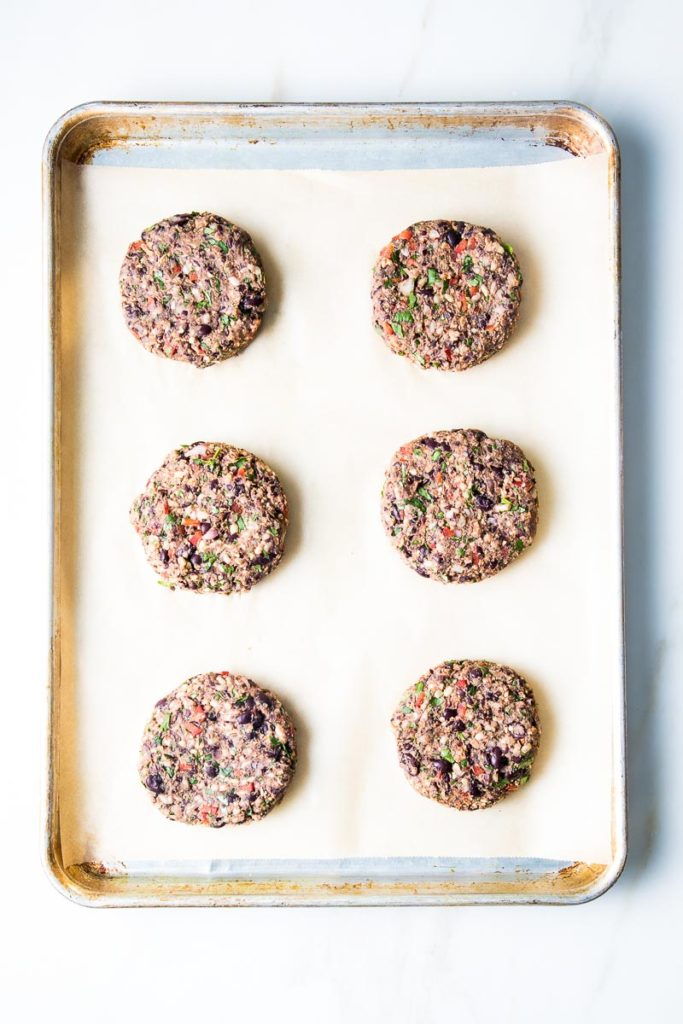 6 black bean burgers on a parchment lined baking tray