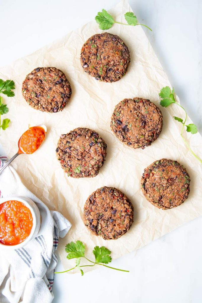 Parchment paper with veggie burgers and a bowl of red sauce to spoon on top.