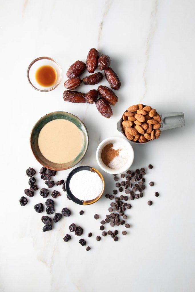 Tahini, Dates, Almonds, arrowroot powder, cinnamon, baking powder, vanilla, chocolate chips and dried cherries artfully arranged.