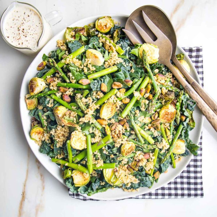 White plate with greens, veggies, crispy quinoa and a creamy dressing.