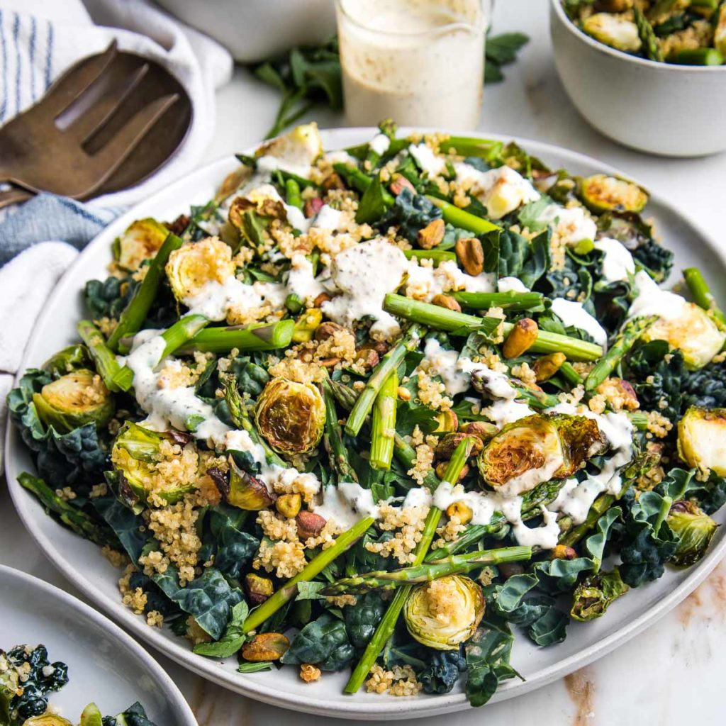 Creamy dressing drizzled on a bed of greens with crispy brussels sprouts and asparagus, pistachios and crunchy quinoa.