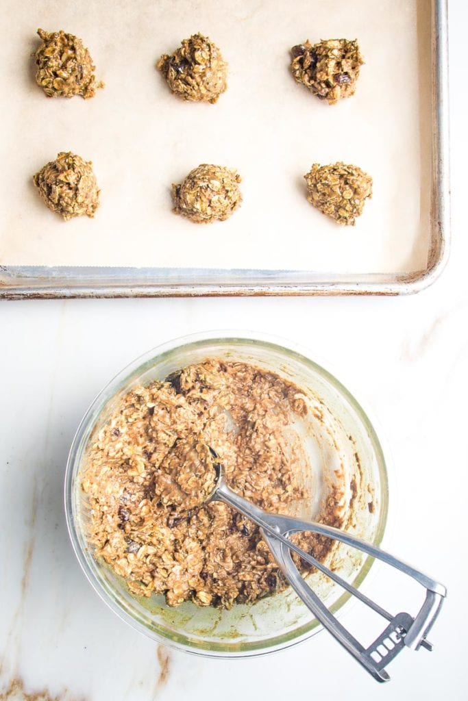 A small ice cream scoop doling out portions of oatmeal cookie dough onto a baking tray lined with parchment.