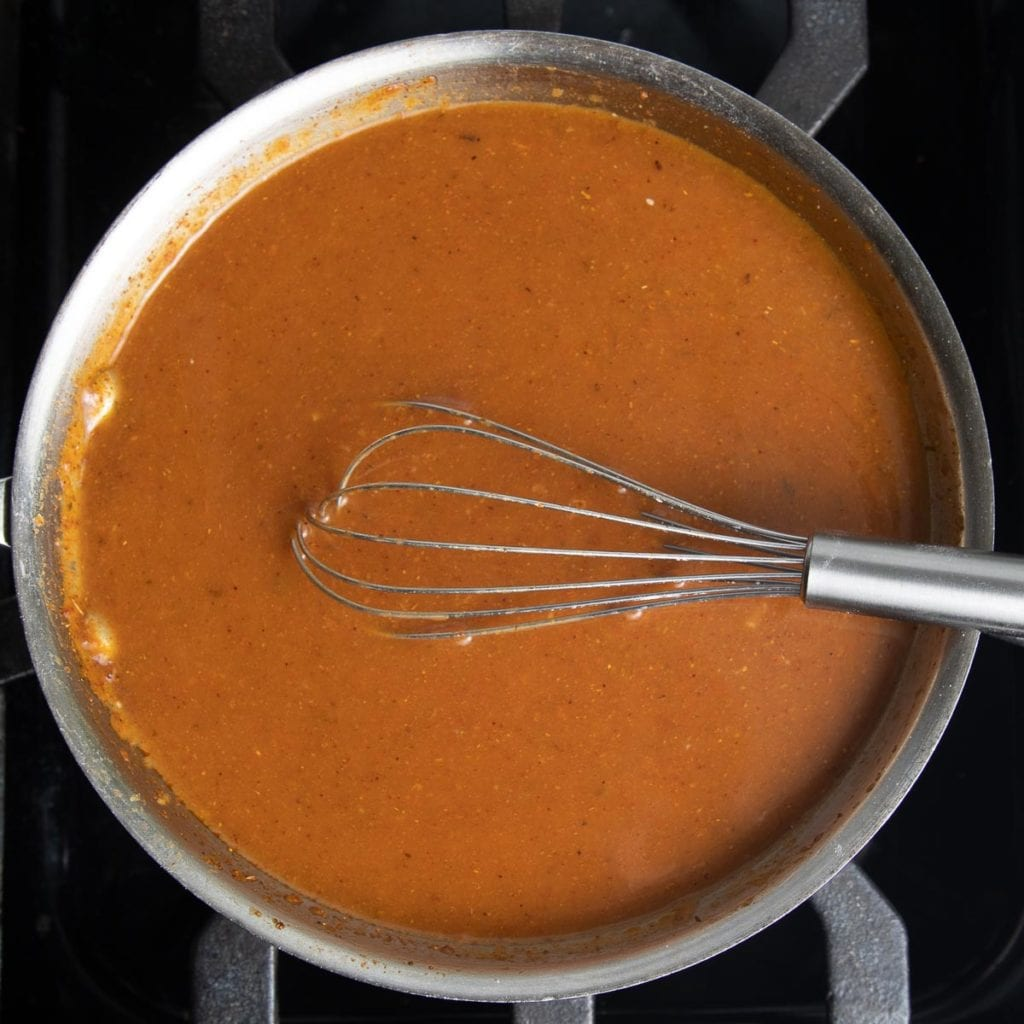 Homemade Red Enchilada Sauce thickening on the stove.