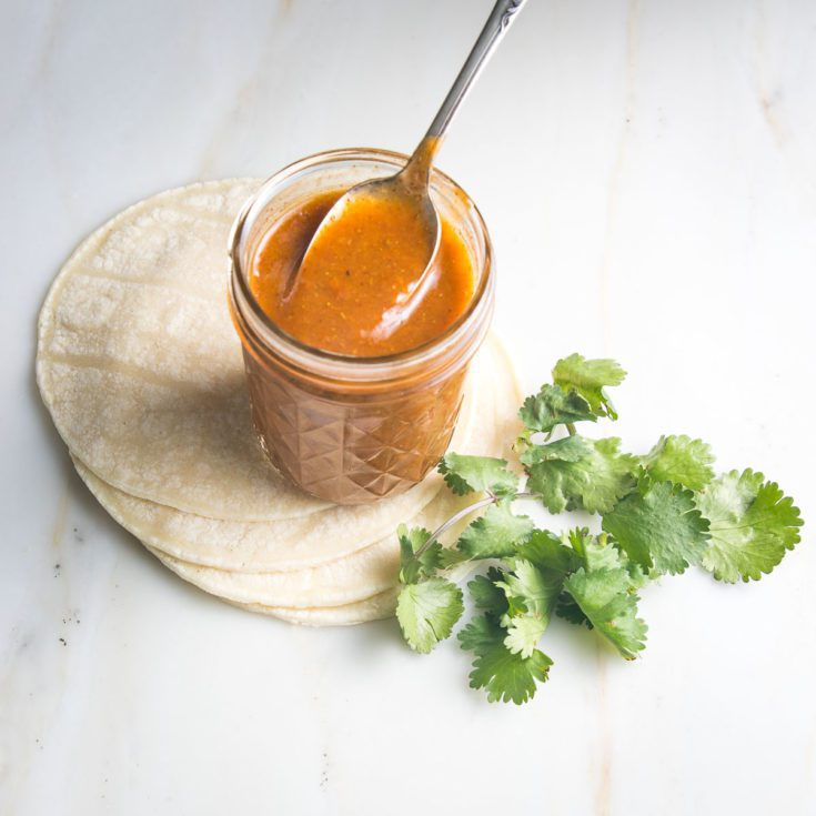 Jar of red enchilada sauce with a spoon in it on top of a stack of tortillas with some cilantro on the side.