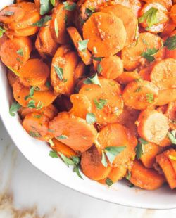 bottom left corner of white bowl with carrot rounds sprinkled with green parsley.