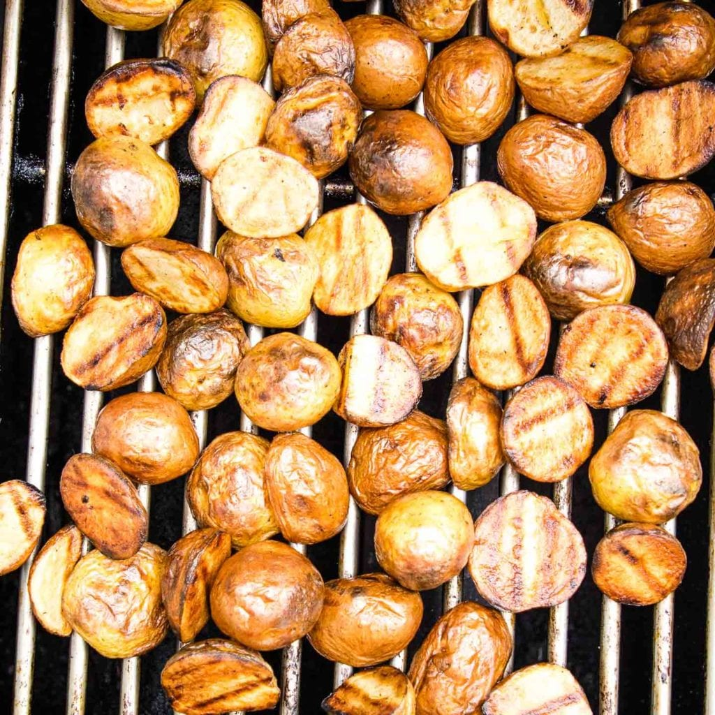 Potatoes on the BBQ, browned and with grill marks.