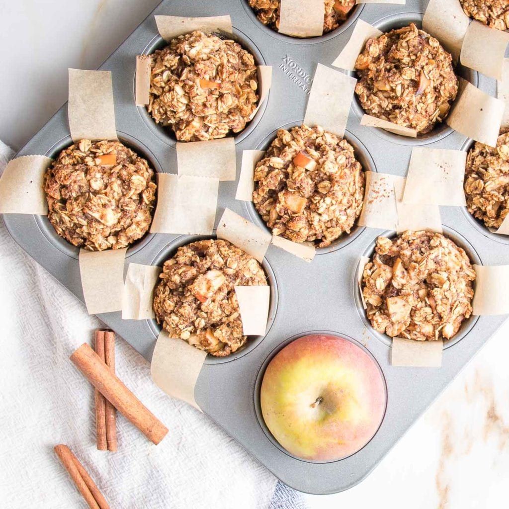 Muffin tin lined with parchment with oatmeal apple muffins