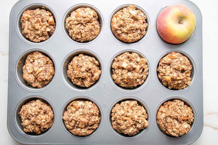 Muffin tin with apple oatmeal chunky muffins and one red apple