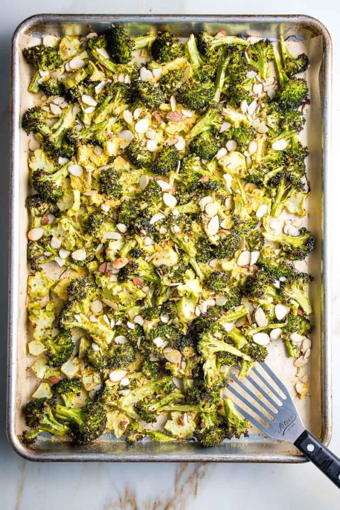 Spatula serving off of a large tray of oven roasted broccoli sprinkled with nutritional yeast.