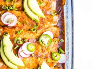 Casserole Dish with enchiladas, garnished with avocado slices, jalapenos and radishes.